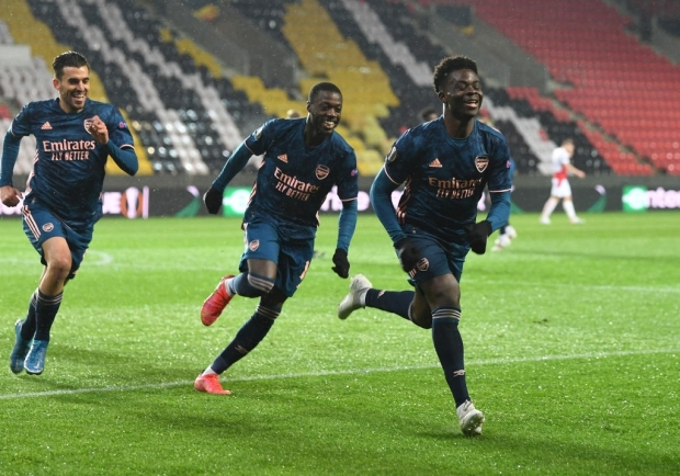 PRAGUE, CZECH REPUBLIC - APRIL 15: (R) Bukayo Saka celebrates scoring the 3rd Arsenal goal with (L) Dani Ceballos and (2ndR) Nicolas Pepe during the UEFA Europa League Quarter Final Second Leg match between Slavia Praha and Arsenal FC at Eden Arena on April 15, 2021 in Prague, Czech Republic. Sporting stadiums around Europe remain under strict restrictions due to the Coronavirus Pandemic as Government social distancing laws prohibit fans inside venues resulting in games being played behind closed doors. (Photo by Stuart MacFarlane/Arsenal FC via Getty Images)