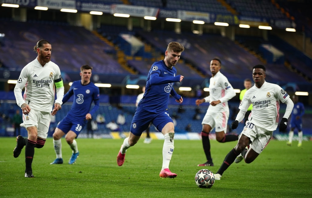 LONDON, ENGLAND - MAY 05: Timo Werner of Chelsea runs with the ball under pressure from Sergio Ramos (L) and Vinicius Junior (R) of Real Madrid  during the UEFA Champions League Semi Final Second Leg match between Chelsea and Real Madrid at Stamford Bridge on May 05, 2021 in London, England. Sporting stadiums around Europe remain under strict restrictions due to the Coronavirus Pandemic as Government social distancing laws prohibit fans inside venues resulting in games being played behind closed doors. (Photo by Chris Lee - Chelsea FC/Chelsea FC via Getty Images )